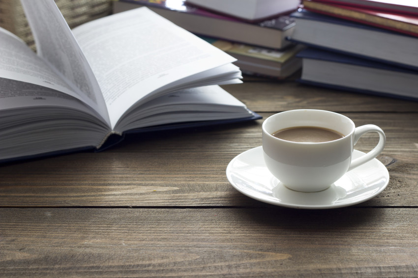 coffee next to a pile of books